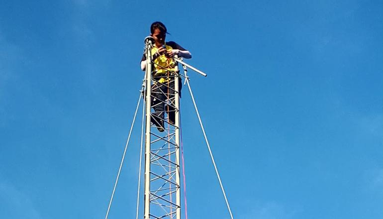 Image description: A person high up on a communications tower