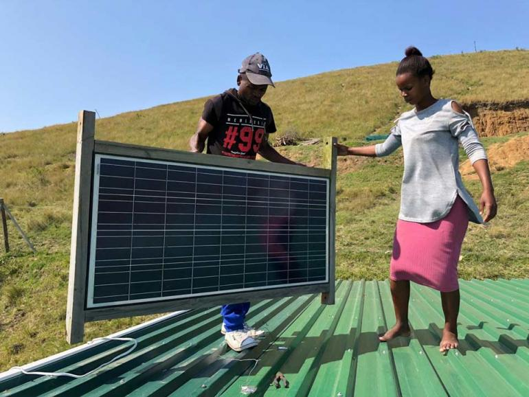 Image description: A man and a woman hold a solar panel on a roof