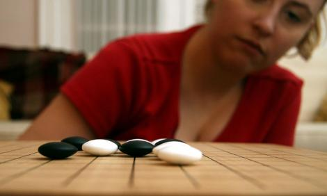 Woman considers a play in a Go board