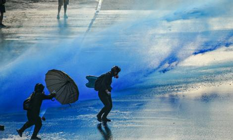 Image description: Water cannons on protestors in HOng Kong