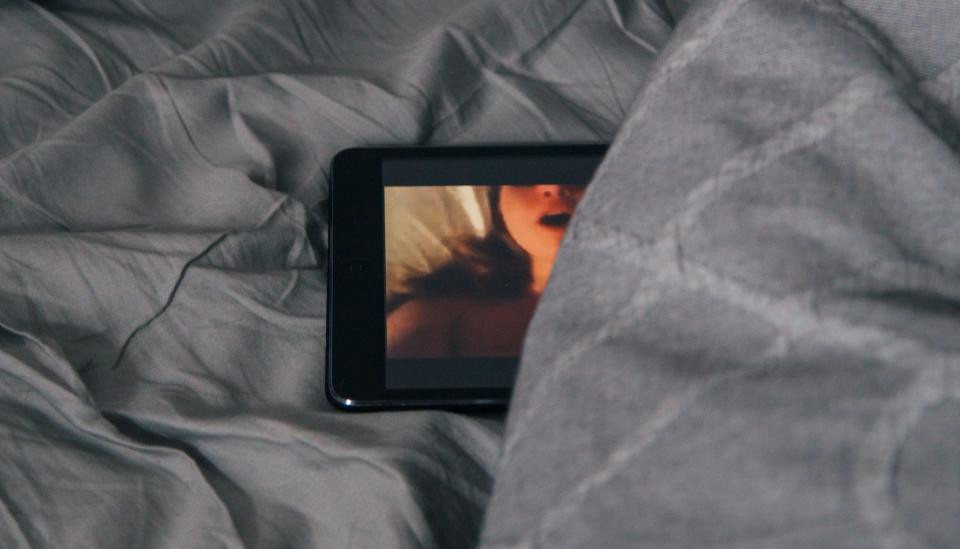 Image description: Tablet lying on bed, image of woman on the screen