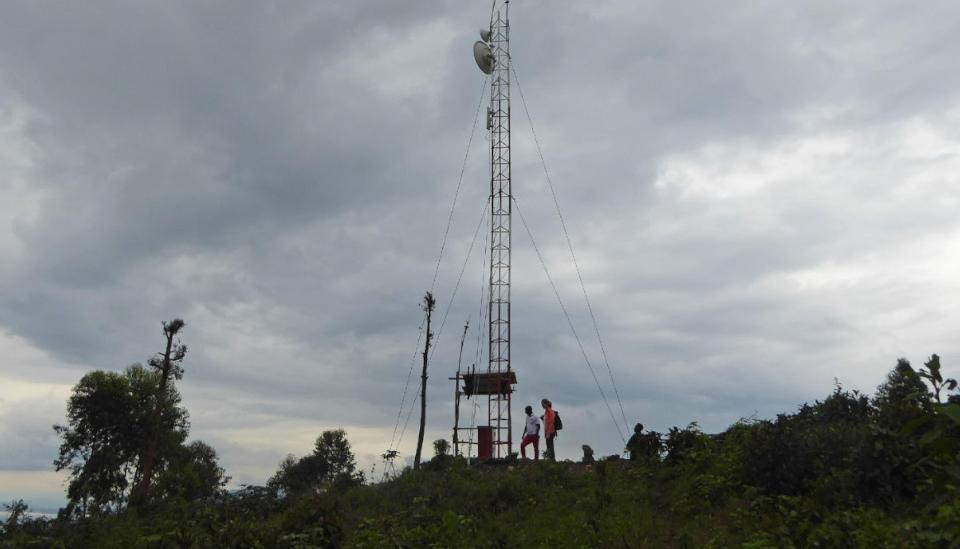 Two people next to one antenna in the mountain